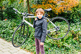 young boy carrying his bike