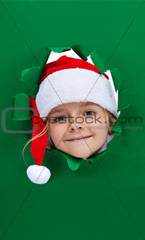 Christmas girl looking through hole in paper