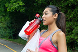 Woman drinks water and rests after running
