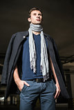 Fashion shot: handsome young man wearing jeans, coat, shirt and scarf