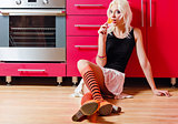 Beautiful blonde girl with candy in hand sits on kitchen floor