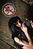 "Beautiful young girl lights a cigarette near ""No fire and smoking"" sign"