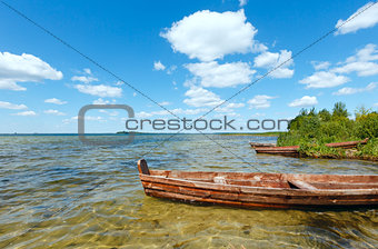 Summer lake view with wooden boats.