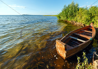 Summer evening lake view with wooden boat.