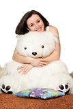 Smiling girl sitting in an embrace with a teddy bear