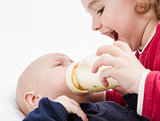 young child feeding toddler with milk bottle