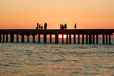 People on the old sea pier during sunset
