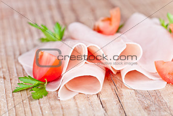 slices of ham with parsley and tomato