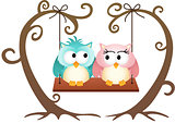 Cute couple owls in love on a swing