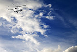 Helicopter in blue sky with clouds