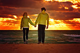 Couple Man and Woman in Love walking on Beach seaside holding hand in hand with Beautiful Sunset sky scenery People Romantic relationship and Friendship concept'