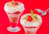 Two strawberry and cream desserts on red background