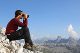 Searching the destination through binoculars in the mountains