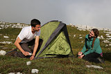 Young people building up a tent in the mountains