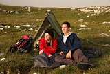 Young couple watching the sunset while camping in the mountains