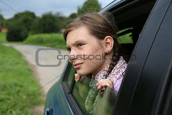 Little girl looking out from the window of a car