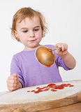 child putting sieved tomatoes on dough