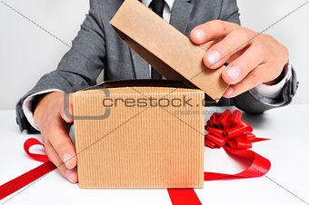 man in suit opening a gift