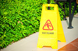 "warning label ""Wet floor"" yellow on the tile floor"