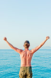 a man with a naked torso is by the sea and put his hands up at dawn