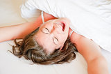 girl in a white bed yawns and stretches in the morning