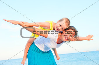 mother and son sitting on her back, happy playing on the beach