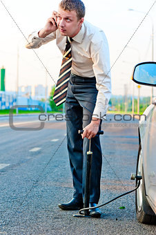 businessman pumps the pump wheel of a car and talking on the phone