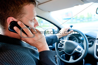 male businessman talking on a cell phone while driving