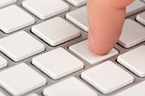 Close-up index finger is pressing a computer keyboard key