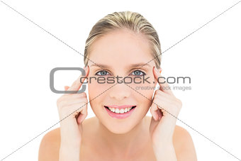 Happy fresh blonde woman touching her temples