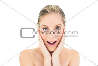 Astonished fresh blonde woman holding her head