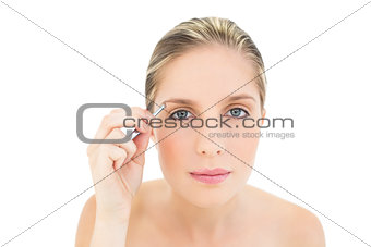 Focused fresh blonde woman plucking her eyebrows