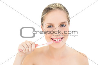 Amused fresh blonde woman brushing her teeth