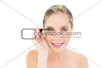 Beautiful fresh blonde woman applying mascara
