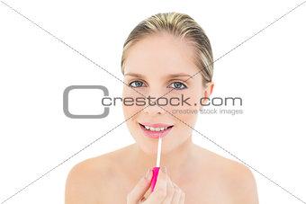 Cheerful fresh blonde woman applying gloss