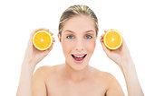 Amused fresh blonde woman holding two oranges halves