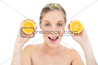 Amused fresh blonde woman holding two oranges halves