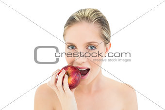 Beautiful fresh blonde woman eating a red apple
