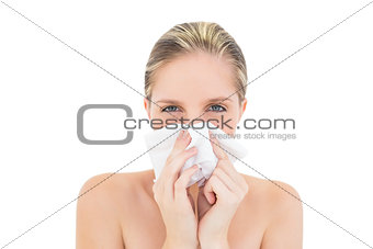 Upset fresh blonde woman sneezing in a tissue