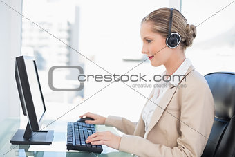 Smiling blonde call centre agent working on computer