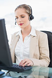 Peaceful blonde call centre agent working on computer