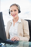 Cheerful blonde call centre agent working on computer