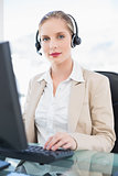 Content blonde call centre agent working on computer
