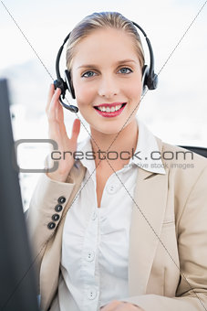 Smiling blonde call centre agent interacting with customer