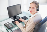 Blonde call centre agent typing looking at camera