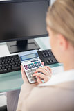 Over shoulder view of businesswoman using calculator
