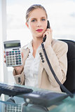 Serious blonde businesswoman on the phone showing calculator