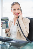 Smiling blonde businesswoman on the phone showing calculator