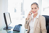 Happy blonde businesswoman having a phone call posing