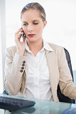 Stern blonde businesswoman having a phone call posing